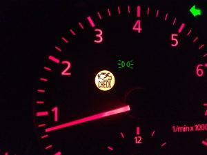 A picture of a auto gauge with the check engine light on.
