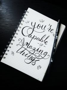 """A picture of a notebook that says, """"You're capable of amazing things."""""""