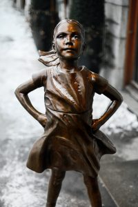 Bronze statue of girl with hands on her hips