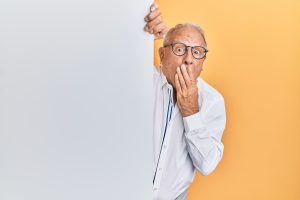 A man covering his mouth in surprise as if he heard something bad.