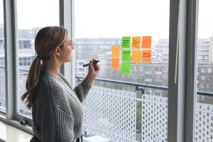 A woman writing on sticky notes that are taped to the wall.