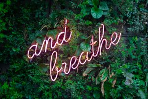 """Neon sign that reads, """"and breathe"""""""