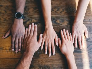 Hands on a table. The hands are of people with different skin tones.