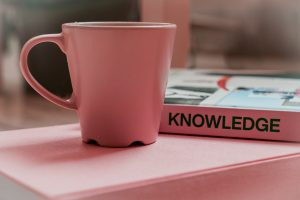 """A coffee cup and a book that says """"Knowledge"""""""
